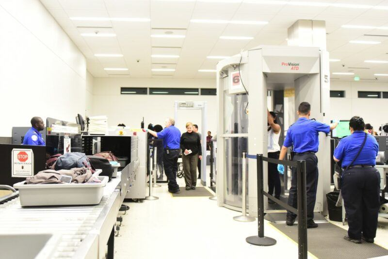 The security screening line at an airport, where the security guards are wearing blue shirt