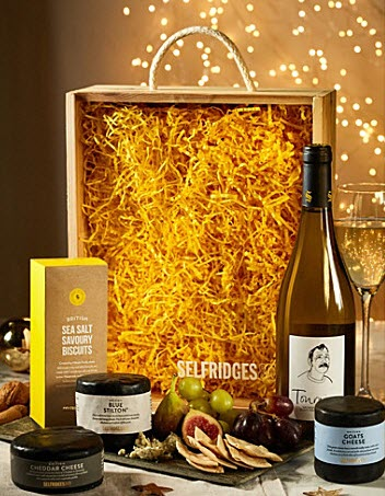 A wooden box with yellow filling, wine and cheese