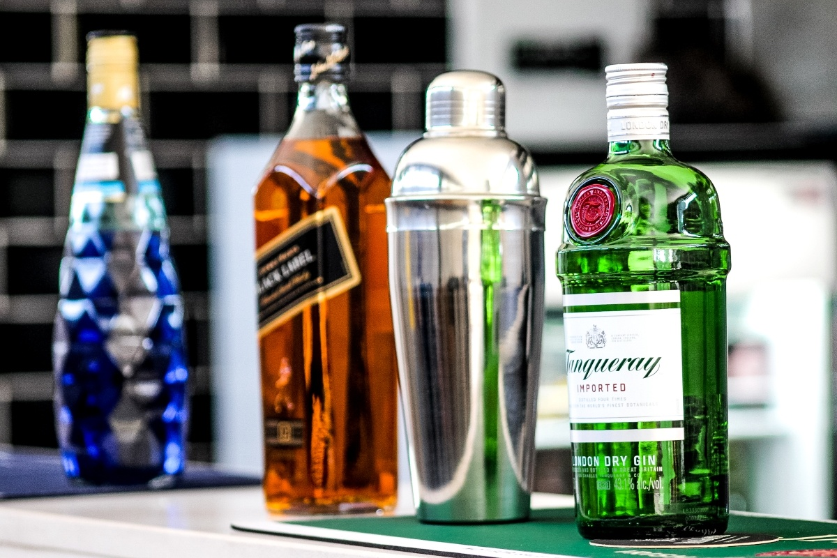 Liquor of the Month Clubs - three bottles of liquor and a skaker sitting on the counter