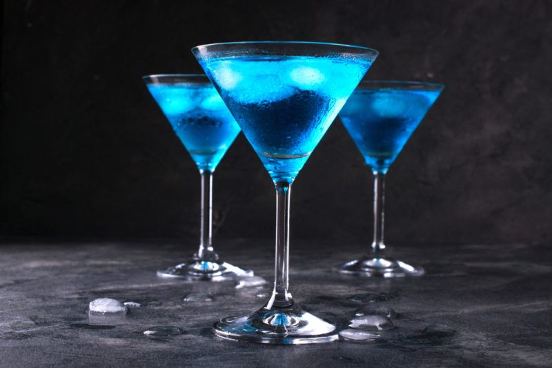 Three electric blue martinis on a gray table against a black background