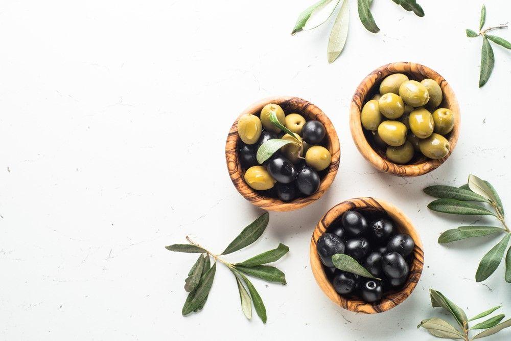 A bowl of black olives, a bowl of green olives, and one of black and green olives
