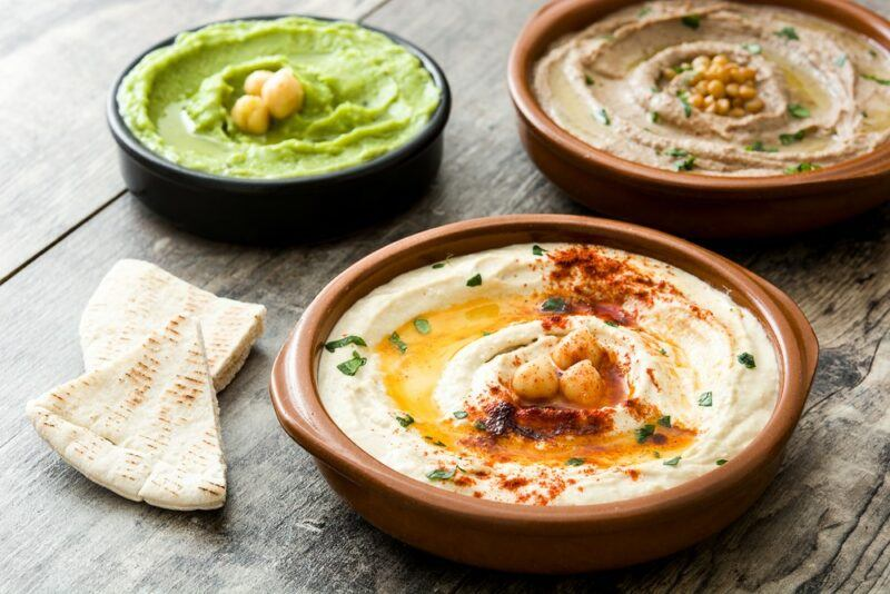 Three bowls of hummus on a wooden table, in different colors