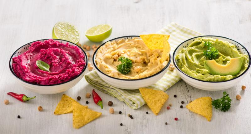 Three white bowls of vegan dip with food to dip in them scattered around