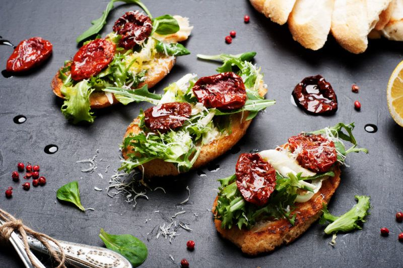 Three pieces of bruschetta on a table with different toppings