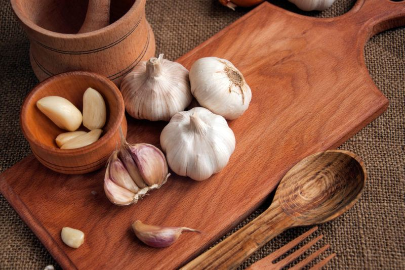 A wooden board with some bulbs of garlic and cloves of garlic in a bowl