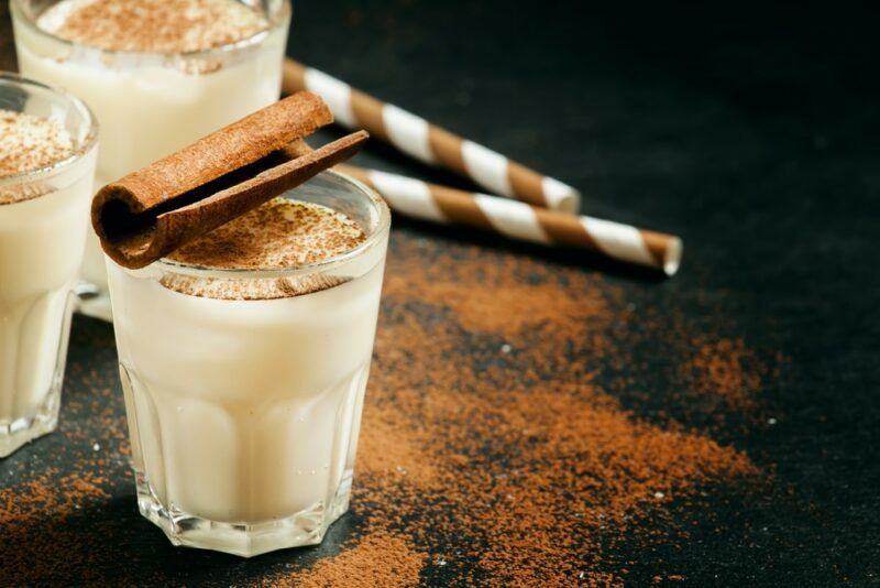 Three glasses of a bourbon milk punch on a black table with straws and cinnamon scattered around