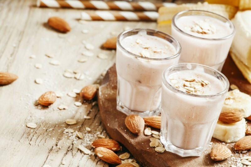 Three glasses of an almond milk smoothie on a wooden board, with straws in the background and almonds scattered around