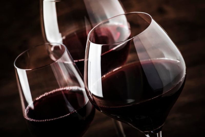 Three glasses of red zinfandel wine where the glasses are different sizes and shapes