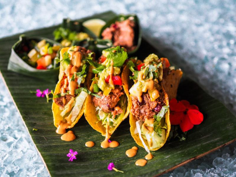 A wooden board with three types of jackfruit tacos