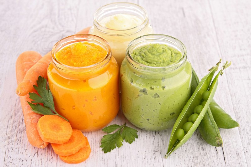 Baby Food Subscription Box - Three jars of natural homemade food, carrot, pea, and pear. Fresh carrots, peas, and parsley sitting along side