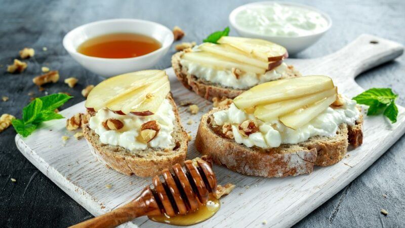 Three pieces of bruschetta on a white plate, with cottage cheese, walnuts, pears and honey