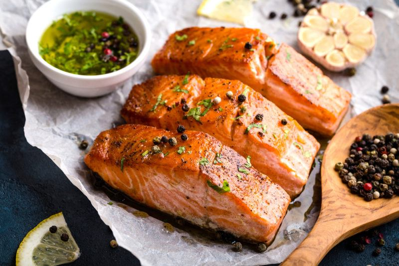 Three pieces of salmon sliced on a piece of parchment paper, with pesto and garlic