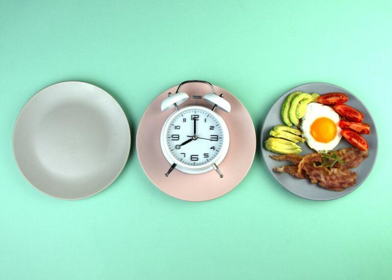 Three plates on a light blue table, one empty, one with a clock, one with food
