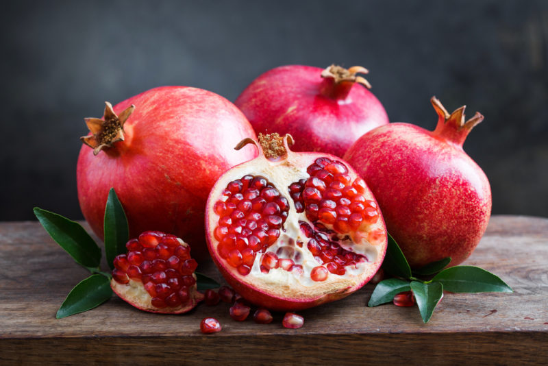 Three pomegranates with a fourth pomegranate that has been sliced open on a wooden board or table