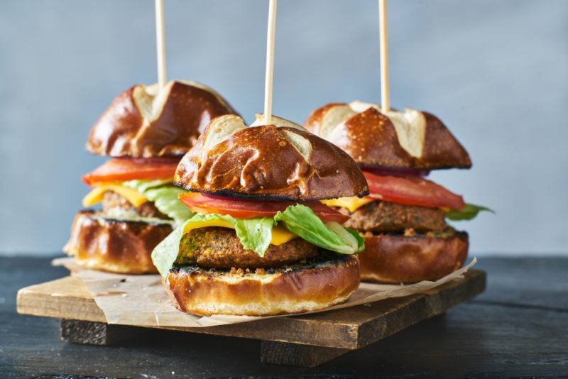 A wooden board with three small burgers with a vegan meat alternative and a skewer stuck through them