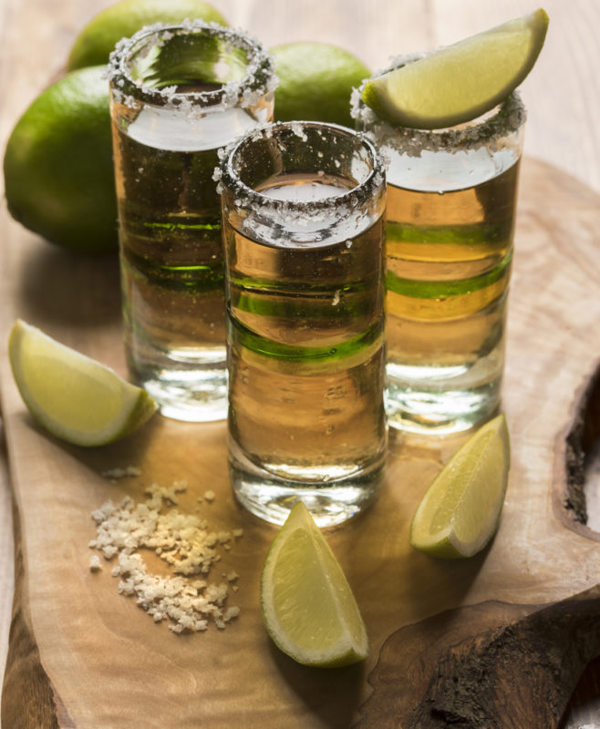 Three tequila slammers on a wooden board with salt and lime chunks
