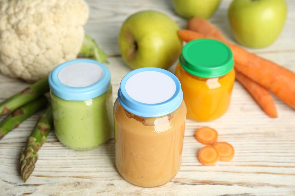 Three jars of baby food with lids, next to cauliflower, apples, and carrots