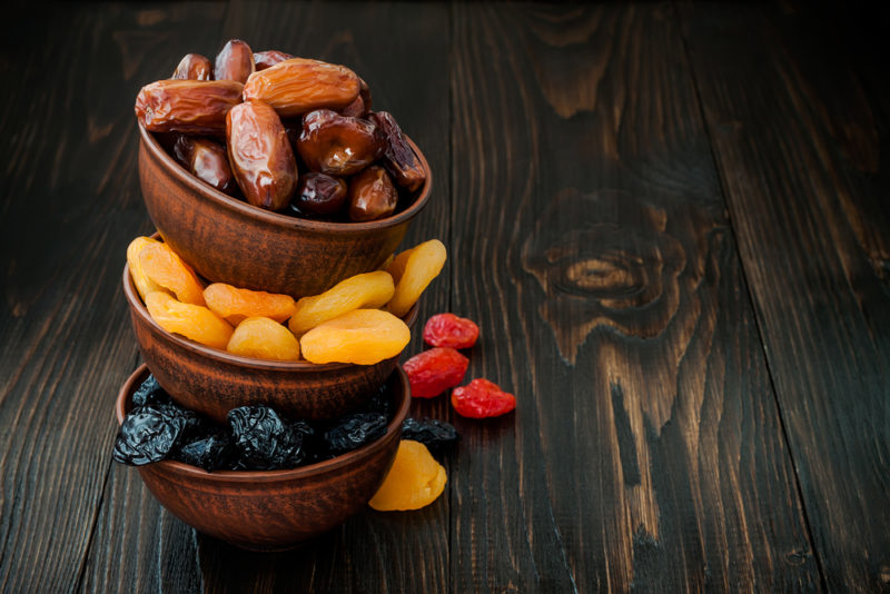 Three wooden bowls of dried fruit stacked on top of one another
