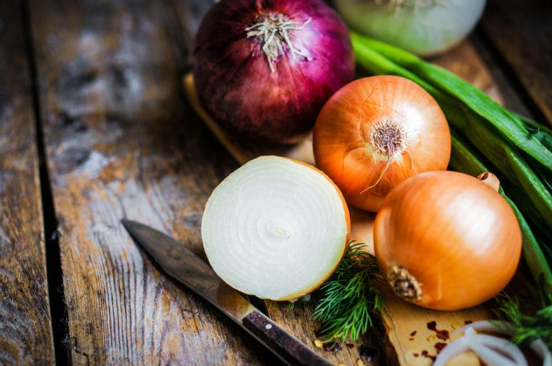 Two white onions, one red onion and haldf a white onion next to a knife