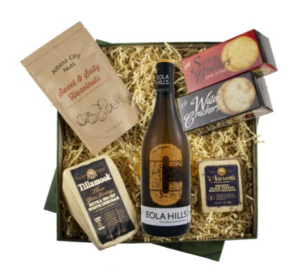 A box with packing material, wine, cheese and crackers