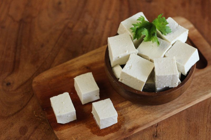 A small bowl of tofu and three separate tofu pieces on a wooden board
