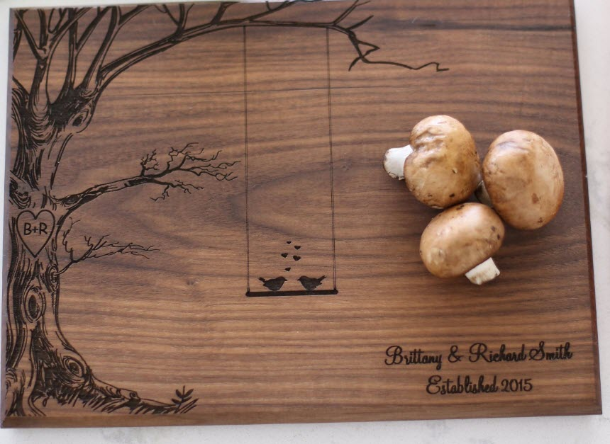 A cutting board with an engraved tree and some mushrooms
