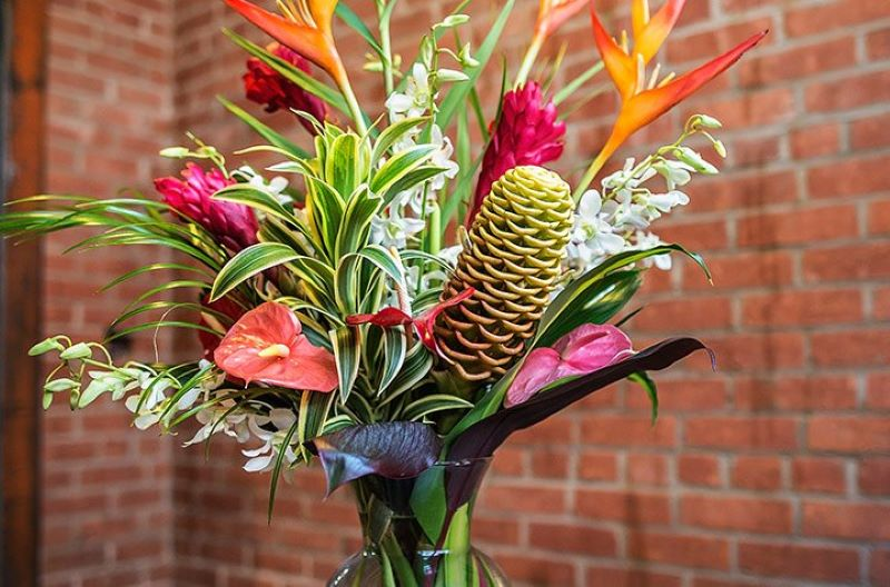 bright colored Tropical flower bouquet in clear glass vase
