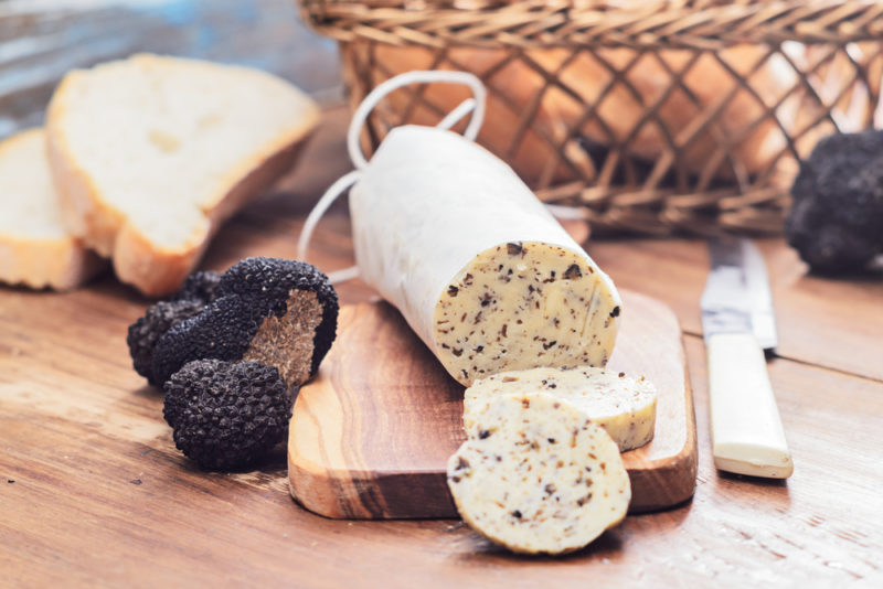 A tube of truffle butter next to black truffles and sliced bread