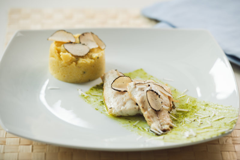 A white dish that contains polenta, white fish and white truffles
