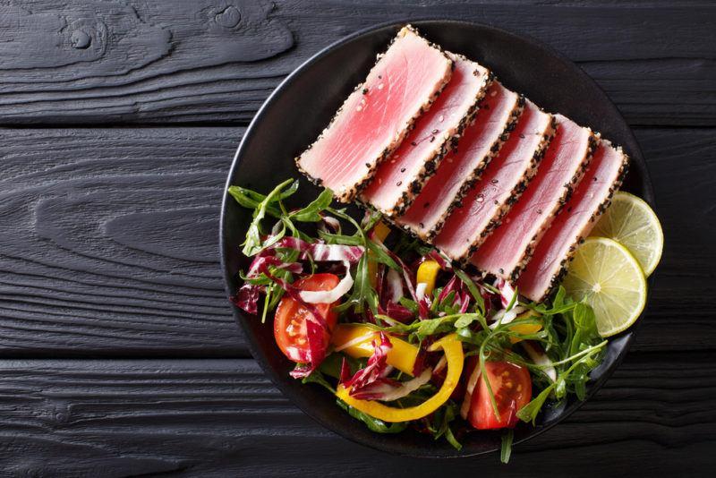 A black bown with veggies and sliced tuna