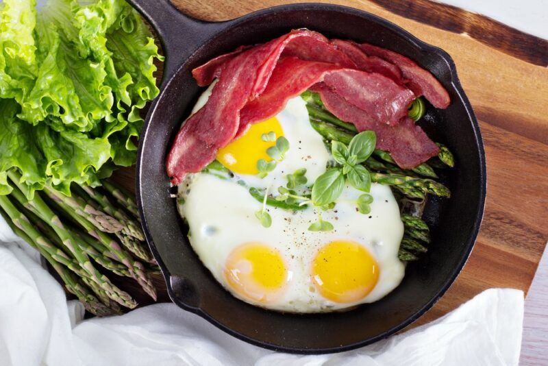 A black frypan with eggs and turkey bacon on a wooden table next to some lettuce
