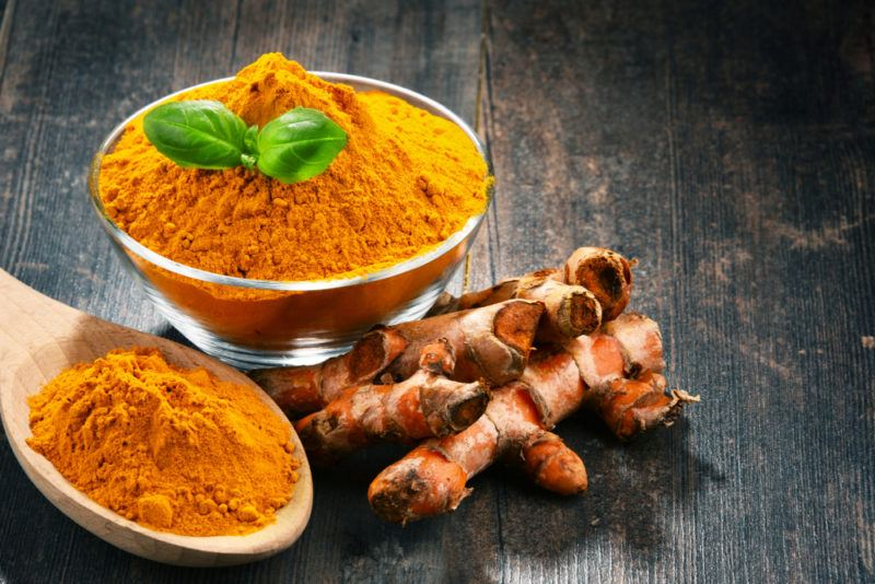 A bowl of turmeric powder, next to a spoon of the powder and turmeric root