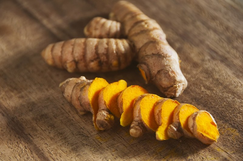 This photo shows a sliced turmeric root next to an uncut turmeric root on a wooden table.