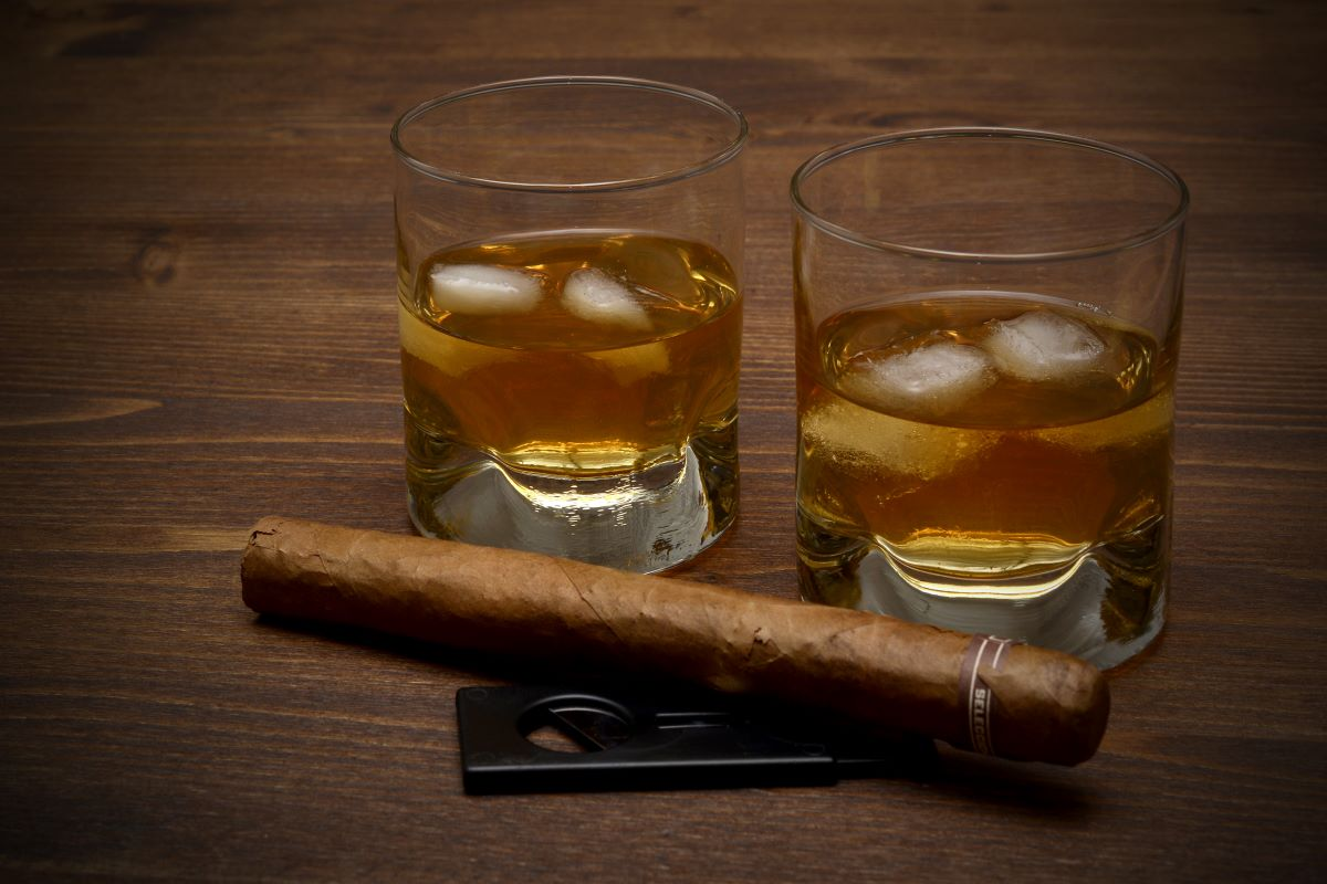 Two glasses of whiskey on the rocks with a cigar sitting in front with a cigar cutter.