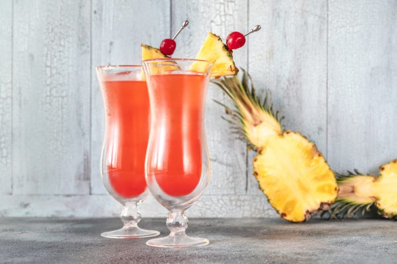 Two tall glasses of a Singapore sling cocktail in front of a wooden wall and a pineapple that's been sliced in half