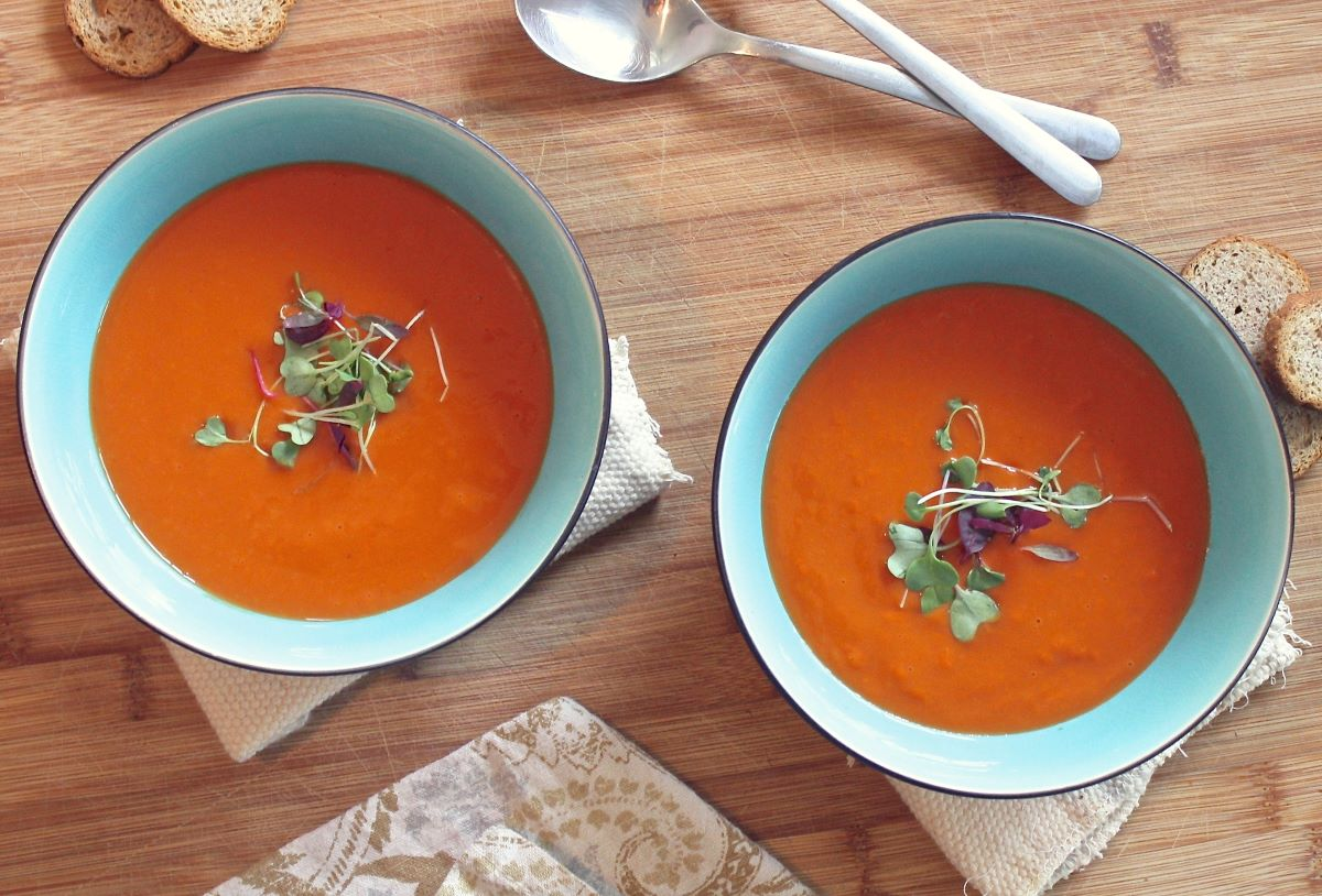 Two blue ceramic bowls with tomato soup garnished with micro greens.  in the background on the table are slices of baguette, two spoons, and linen napkins