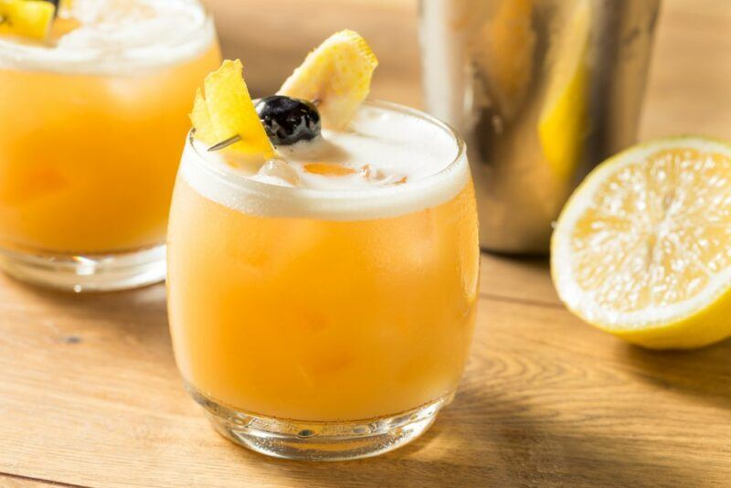 Two amaretto sour cocktails on a table, garnished with citrus