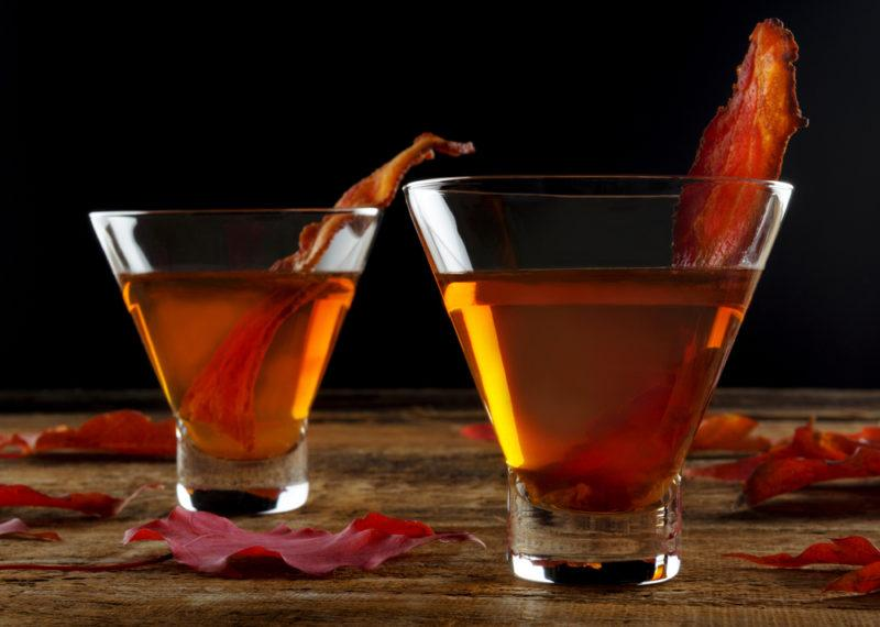 Two whiskey cocktails with bacon as a garnish