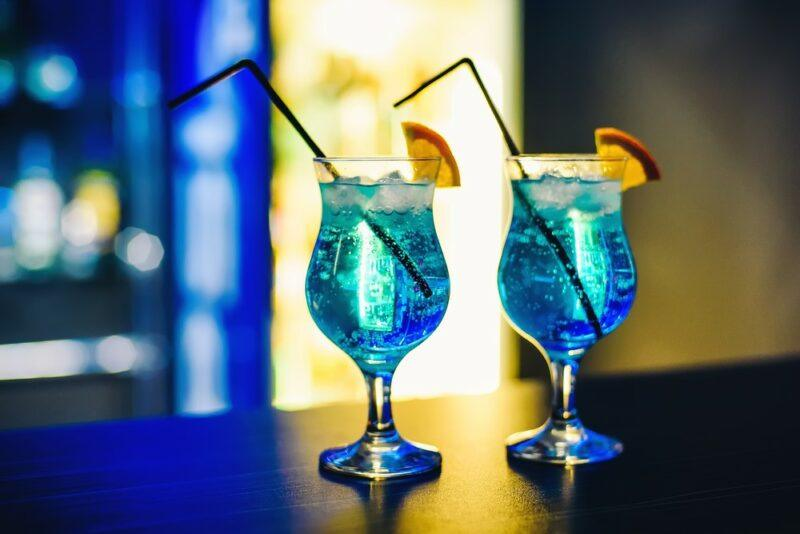 Two blue curacao cocktails sitting on a bar with citrus wedges and straws