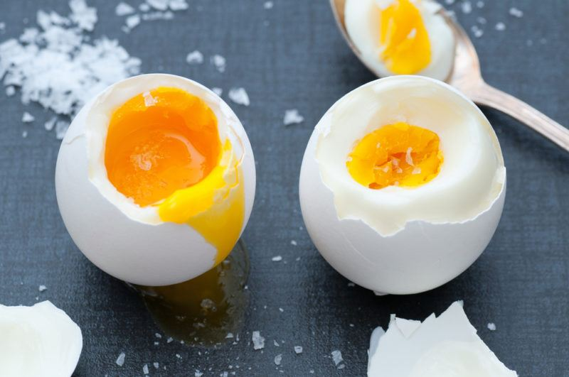 Two boiled eggs on a black background with a spoon and salt