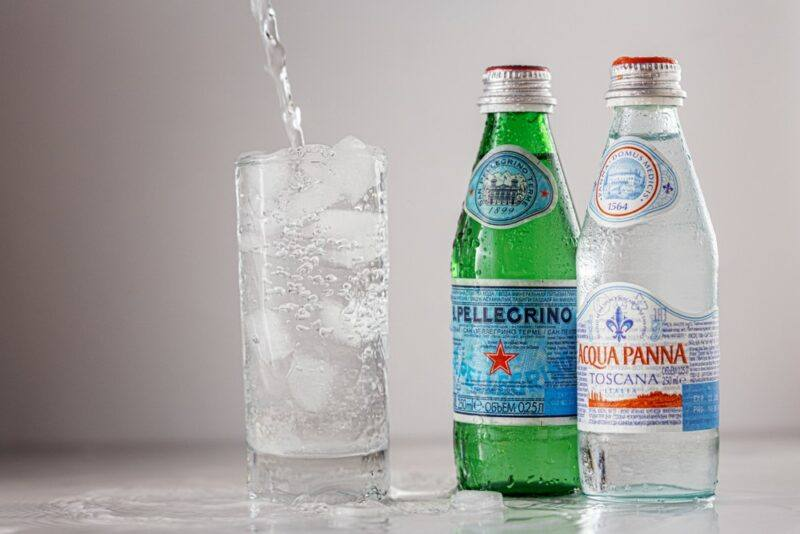 Two bottles of sparkling mineral water on a table next to a glass of sparking mineral water with ice and a straw