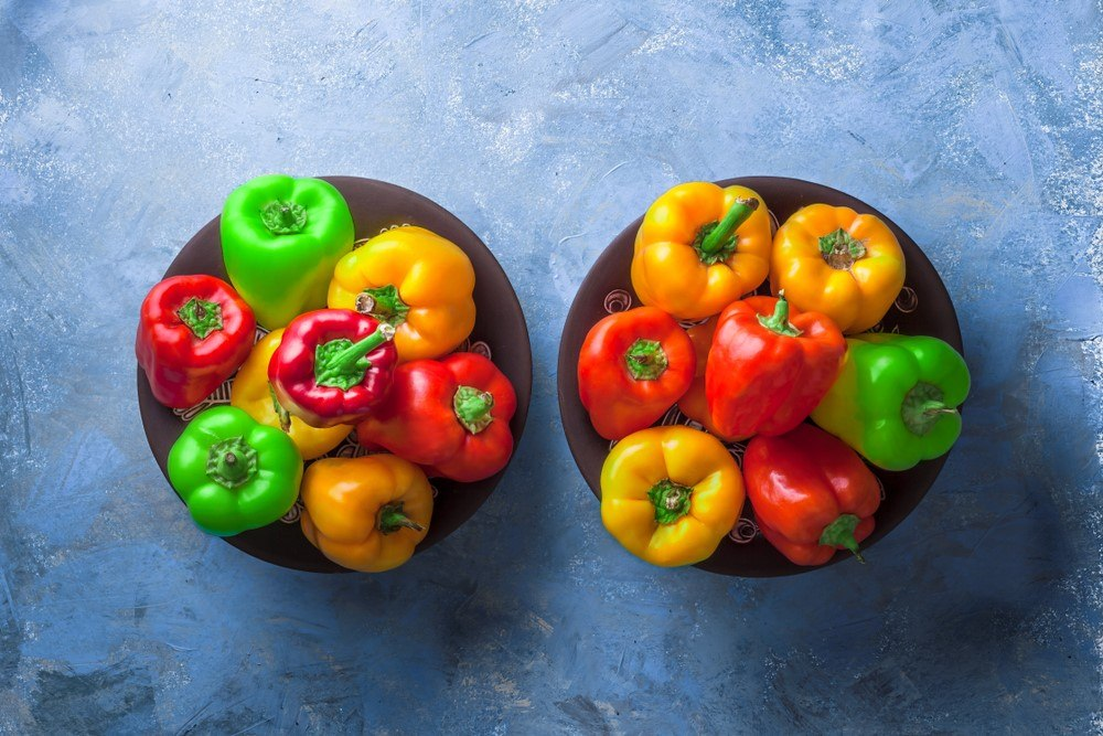 Black bowls with a selection of red, yellow, and green bell peppers