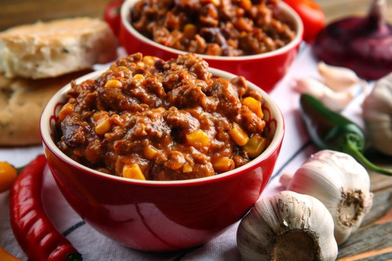 Two red bowls full of chili, with some chili ingredients scattered on the table