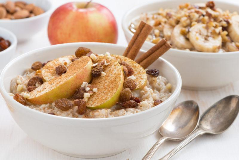 Two bowls of oatmeal with apples, raisins, and cinnamon, next to an apple, two spoons, and some small bowls of ingredients