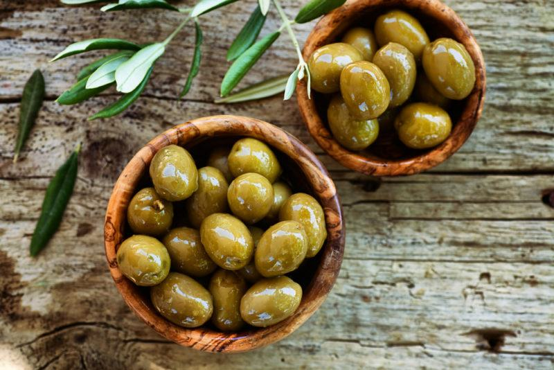 Brown bowls that contain green olives on a wooden background