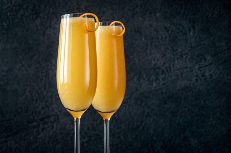 Two champagne glasses with a bucks fizz cocktail and a twist of citrus, in front of a black background