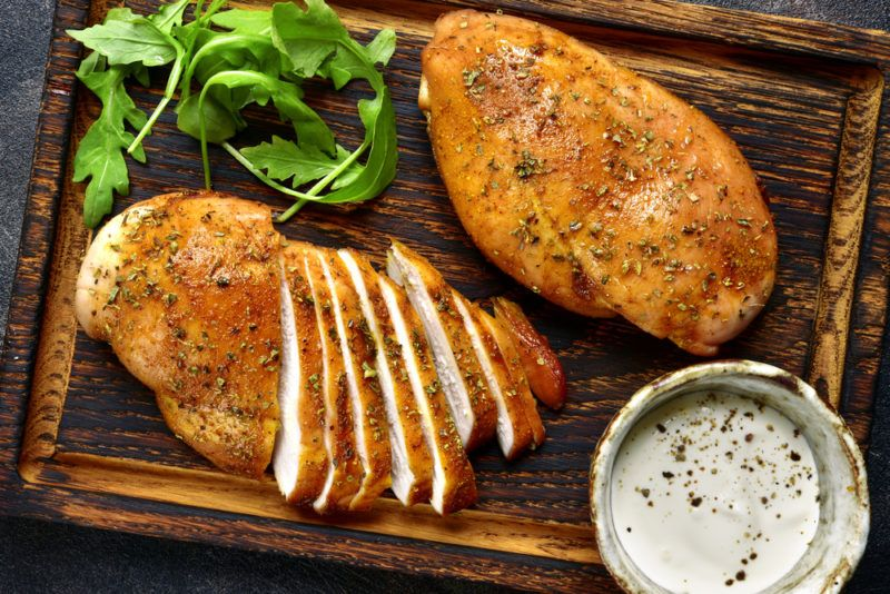 A wooden board with two chicken breasts, some herbs, and a small container of dip. ONe of the chicken breasts has been sliced