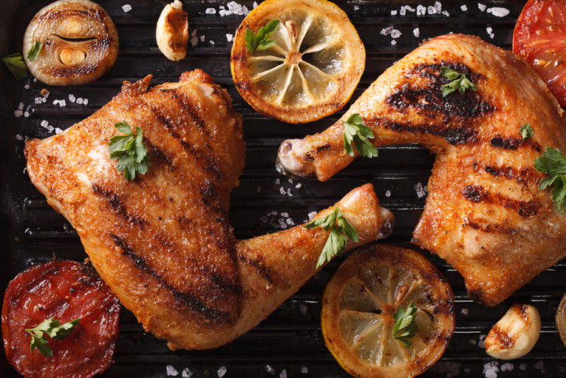 Two grilled chicken legs with thighs on a black background with some lemon slices