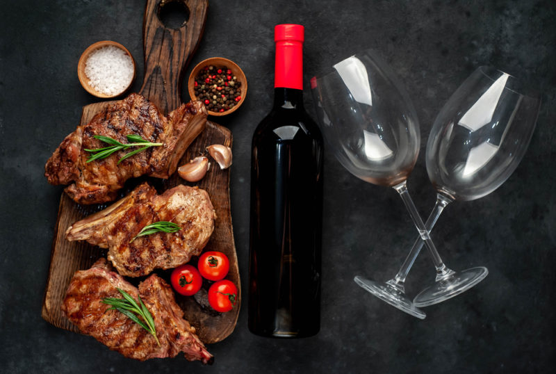 A wooden board with bbq steak, a bottle of red wine, and two glasses