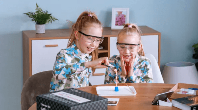 Two girls sitting at table working on a science project